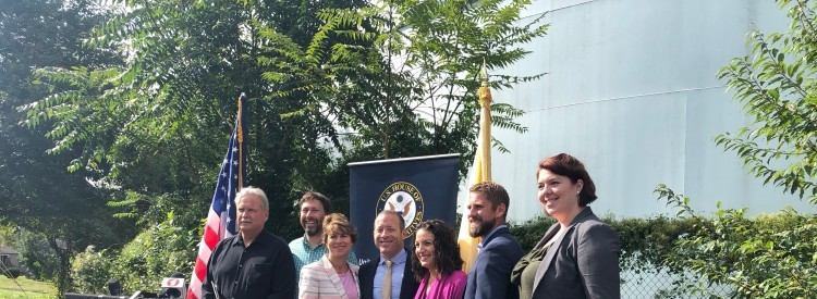 Congressman Gottheimer and environmental advocates stand behind the podium at the superfund site.